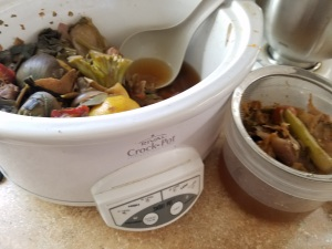 Separating cooked scraps from the broth.